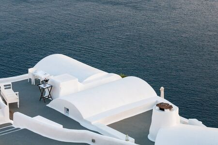 Santorini traditional charming white architecture, and blue sea Cyclades Greek islands, Greece.