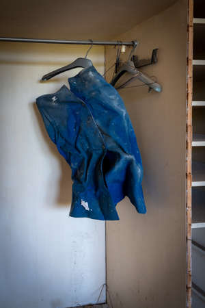 Abandoned bedroom with old used skirt hanging on the wardrobe