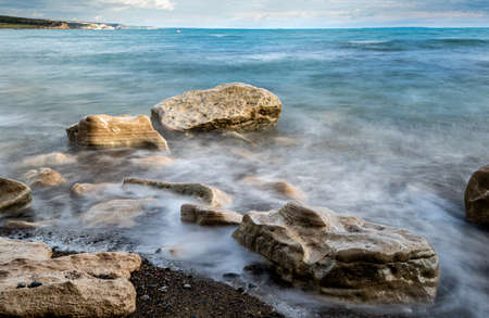 Seawaves splashing onto the sandy coast with pebbles and blue cloudy sky.