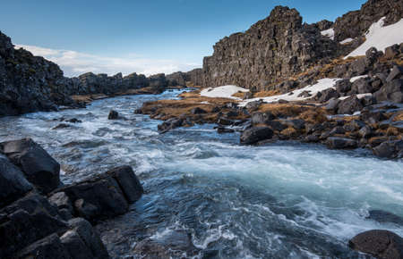 Water from waterfall splashing on a rocky river Iceland