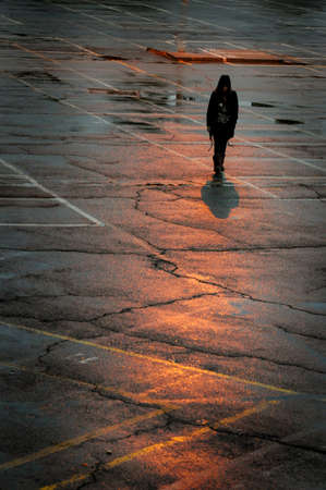 Walking shadow of an unrecognized person walking in streets after rain