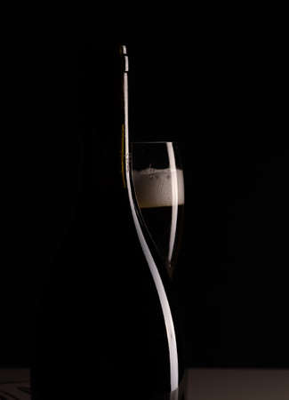 Red sparking wine on a wineglass and silhouette of black wine bottle. Stockfoto