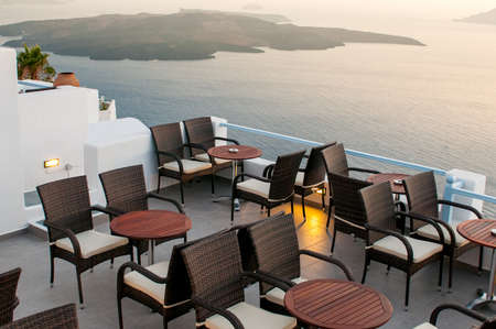 Roof garden cafe restaurant at the caldera in the Aegean sea at sunset. Santorini island Greece