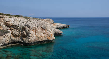 Rocky coastline with blue water and sky.