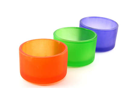 Colored candle holders on white background