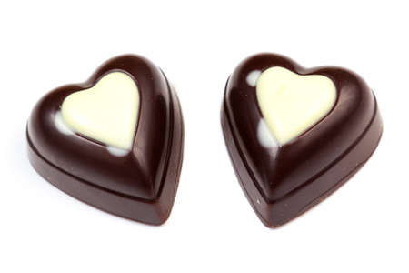 Two chocolates in form of heart on white background