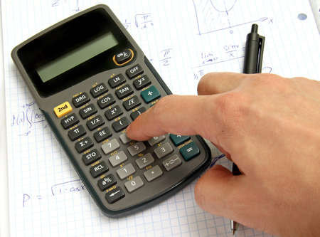 Scientific calculator on notebook paper and a hand Stock Photo