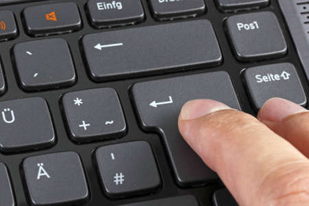 Close up of a finger pressing enter Stock Photo - 13539042