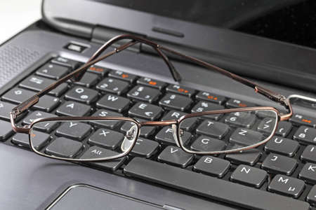 Glasses on a laptop keyboard Stock Photo