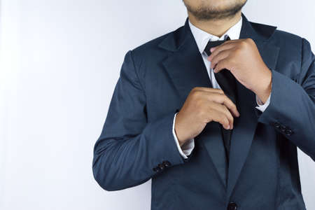 Someone who plays the role of a businessman, he is fixing his tie Imagens