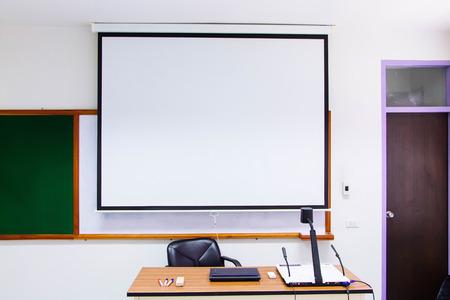 Die Vorderseite des Klassenzimmers verfügt über eine Projektionswand und einen Schreibtisch mit einem Notizbuch, einem Visualizer und einem Whiteboard-Marker sowie einem Pinsel zum Entfernen der Tafel.