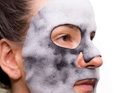Isolated girl with cleansing mask on the face.