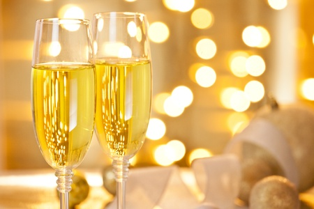 Close-up photograph of two glasses of champagne set on a table decorated with christmas ornaments