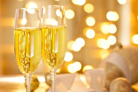 Close-up Fotografie von zwei Gläsern Champagner-Set auf einem Tisch mit Weihnachtsschmuck dekoriert