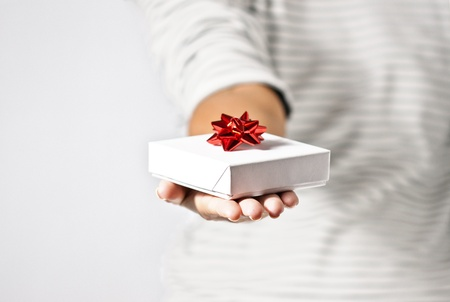 Close-up photograph of a young woman handing a gift  Stock Photo