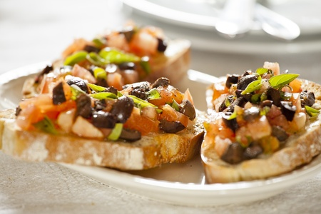 Close up photograph of three tomato and olives bruschetta