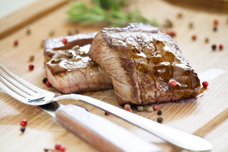 Close up photograph of two steaks on a wooden board