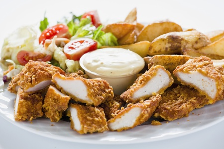 chicken nuggets: Photograph of Tasty meal with Chicken Nuggets Potatoes and Salad Stock Photo