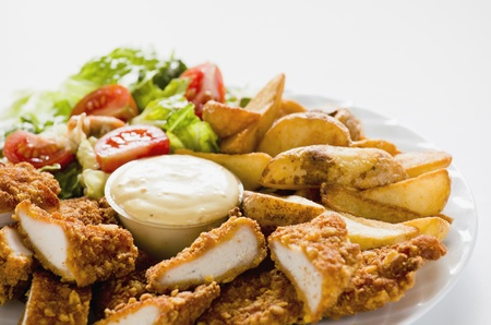 Photograph of Tasty meal with Chicken Nuggets Potatoes and Salad Stock Photo