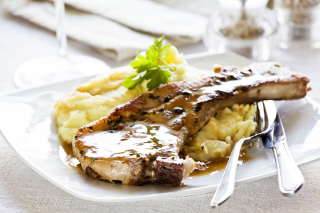pork chop: Photograph of a pork chop with mashed potatoes meal