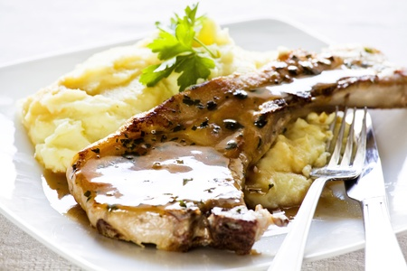 Photograph of a pork chop with mashed potatoes meal