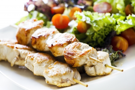 Close up photograph of three chicken skewers served with salad