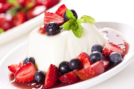 Close up photograph of a panna cotta dessert with strawberries and blueberries