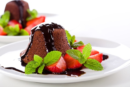 Close up photograph of a chocolate souffle with strawberries