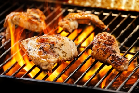 Close up photograph of chicken pieces on the barbecue