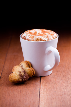 Close up of a cup of cappuccino coffee with two heart shaped cookies Stock Photo