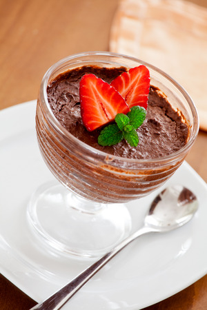 Close up of a bowl of chocolate mousse with strawberries