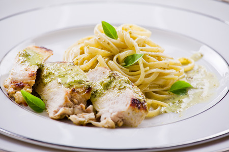 roasted chicken: Close up photograph of a pesto pasta with chicken meal Stock Photo