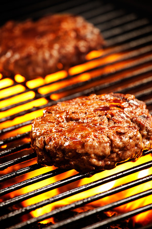 Close up photograph of two grilled beef burgers