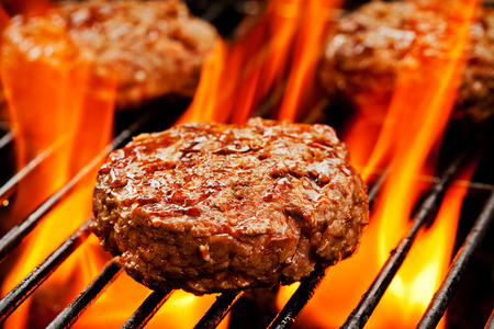 grilled meat: Close up of three burgers on the grill