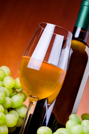 Photograph of a glass of white wine with grapes