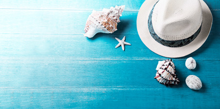Summer hat and sea shells on a wooden table Standard-Bild