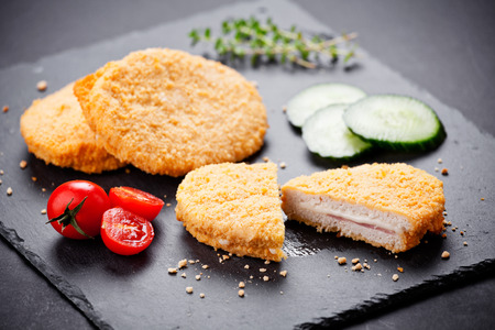 Three tasty cordons bleus served with cucumbers and tomatoes