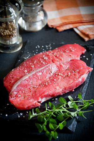 rib eye: Two rib eye steaks on a slate plate with spices