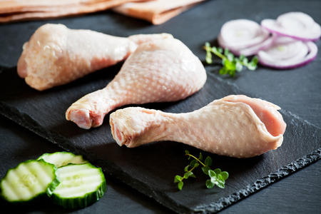 Three raw chicken drumsticks ready to be cooked