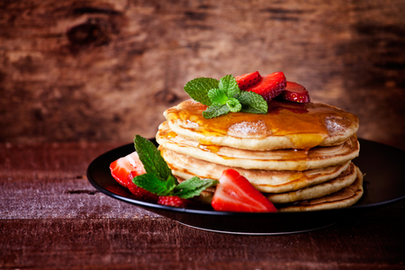 Bunch of homemade pancakes with strawberries and honey