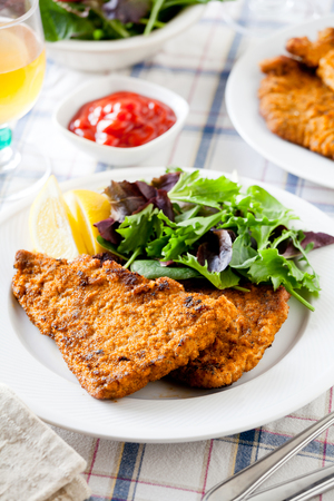 Homemade breaded pork schnitzel with some green salad