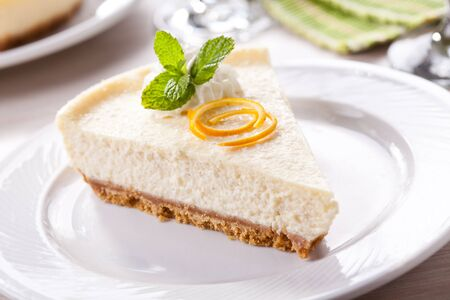 Slice of a homemade cheesecake with whipped cream and fresh mint