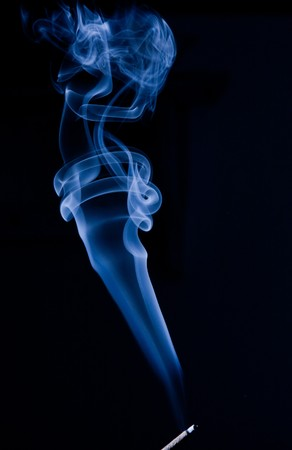 Blue smoke drifting up from incense stick, on black bacground