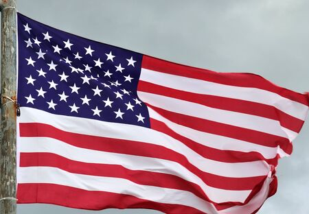 Close up view at a national USA flag moving in heavy wind Stock Photo