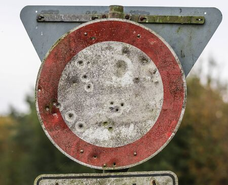 Detailed close up view on bullet holes of gunshots at a traffic sign Stock Photo