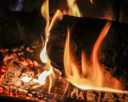 Close up on a crackling warm camp fire burning with red and orange flames Standard-Bild