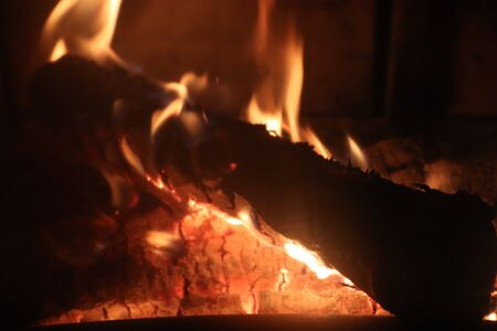 Close up on a crackling warm camp fire burning with red and orange flames