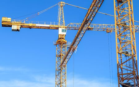 Big yellow cranes at a construction site in Kiel Germany on a sunny day with a clear blue sky