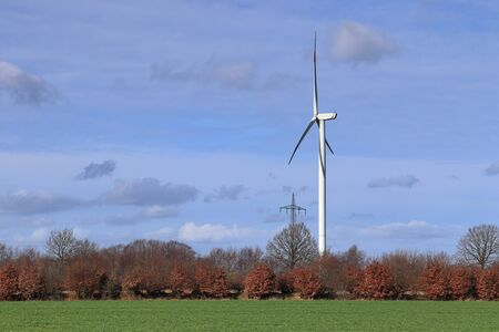 View on alternative energy windmills in a windpark in northern germany in front of a blue sky