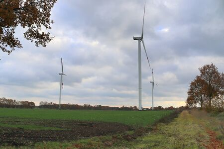 View on alternative energy windmills in a windpark in northern germany in front of a blue sky Banco de Imagens